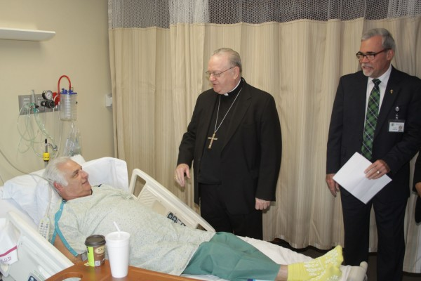Bishop Dennis Sullivan visits Deacon Michael D'Ariano of Sewell, NJ during his visit to Kennedy Hospital. Deacon Gerard Jablonowski looks on.