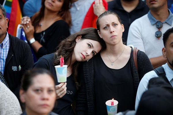 Women hold candles during a June 13 vigil in Los Angeles for the victims of the mass shooting at the Pulse gay nightclub in Orlando, Fla. A lone gunman, pledging allegiance to the Islamic State terrorist group, killed 49 people early June 12 at the nightclub. (CNS photo/Lucy Nicholson, Reuters) See ORLANDO-PRAYER-VIGIL June 14, 2016.