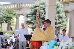 Father Jon Thomas, , offers Eucharistic benediction at the Kennedy Plaza following the ceremony at the surf.